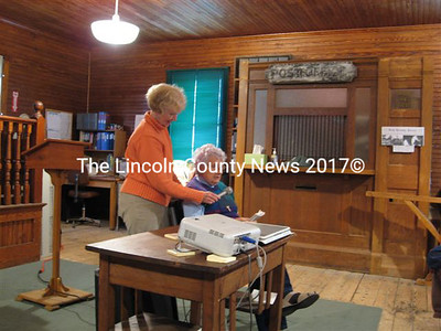 Libby Harmon of the Whitefield Historical Society (left) holds the microphone for her aunt Lydia Chase, 93, as the older woman shares an eyewitness account of the 1948 fire in North Whitefield village.