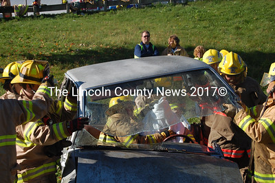 Bristol and South Bristol firefighters lift the roof of a Mazda pickup as a firefighter inside administers first aid to the driver in an Oct. 17 training exercise. (J.W. Oliver photo)