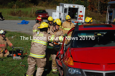 A firefighter cuts away the remainder of a mangled Pontiac Vibe door. (J.W. Oliver photo)