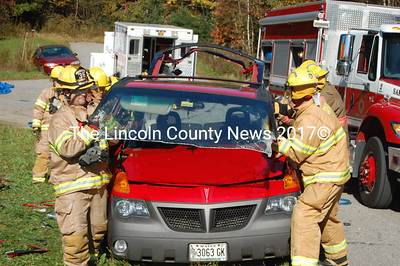 A team of firefighters lifts away the Vibe's roof. (J.W. Oliver photo)