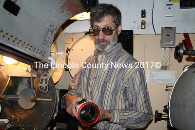 Harbor Theatre operations director Jason Sheckley holds an anamorphic lens in the projectionist's booth of the Harbor Theatre in Boothbay Harbor. (Matthew Stilphen photo)