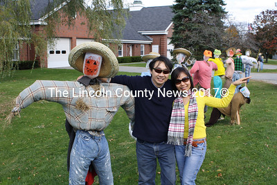 """Binh (right) and Trung Quach of Los Angeles, Cal. pose with a scarecrow Oct. 18 in front of the Wiscasset municipal building. """"We were driving through and saw what we thought were protesters,"""" said Trung Quach. The couple was visiting Maine for the first time."""