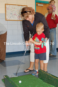 Carson and his mom try to sink a putt on the green in the kids' activity section of Applefest on Oct. 2. (Alex Toy photo)