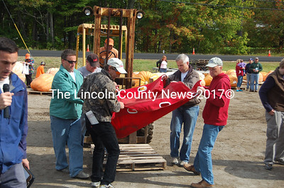 Volunteers carefully transfer a giant pumpkin from its pallet onto the scales. (J.W. Oliver photo)