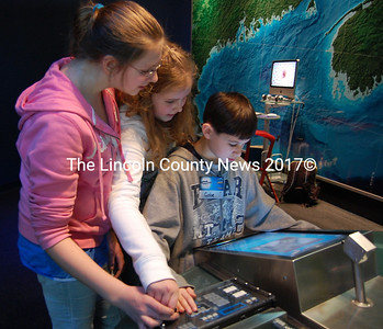 Julia Fasano, 11, Emily Brown, 11, and Gabe Solorzano, 12, students at Jefferson Village School, position an underwater camera to take pictures of lobsters during a class trip to the Gulf of Maine Research Institute in Portland on Feb. 9. (Alex Toy photo)