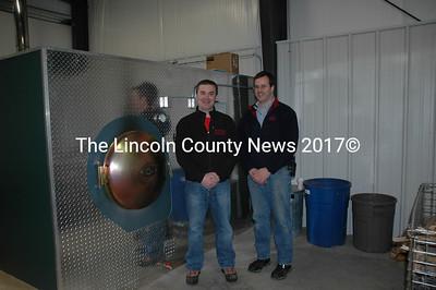 Jon Poland and Rob Gardiner show off the new wood fired boiler that provides heat for Damariscotta Hardware. (Joe Gelarden photo)