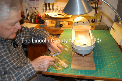 "Albert Waltz of Wiscasset is working on a model of research vessel the ""Abel-J"", built by Goudy and Stevens shipyard in E. Boothbay. In the back on a swivel stand is a solid hull Hudson River Sloop. (J Maguire photo)"