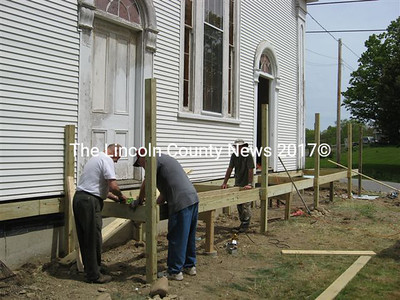 (Left to right) Earl Lemieux and Dick Parten and Charles Jones, two workers from Saraland, Ala., replace the porch and ramp at the Sheepscot Valley Community Church on Tuesday. Not pictured but also helping with the project were Mike Bedford, of Saraland, and associate pastor Dan Coleman, of Augusta.
