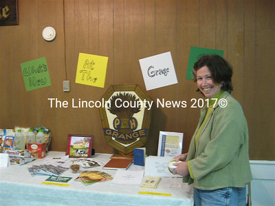 "New Arlington Grange member Beth Whitman, of Whitefield, stands by the table showing ""what's new at the grange."" Public suppers using locally grown farm-fresh food will begin June 12."