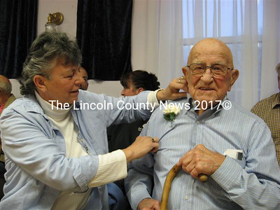 Sharon Clark pins a carnation on father Alden Boynton's shirt prior to the Arlington Grange awards ceremony last Wednesday evening.
