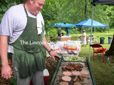 Fireman Ron Theriault of the Dresden Fire Department grills up some burgers and brats for scores of hungry guests Saturday at the Dresden Summerfest. (A.Brodsky photo)