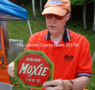 John Leheney, official historian of the Moxie Congress, shows off one of his antique Moxie signs. Some Moxie memorabilia is extremely valuable, Leheney said. (Alex Toy photo)
