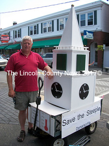 Steeple Fundraising Committee Chairman Walter Hilton stands beside a model of the steeple outside the Maine Coast Book Shop July 26. (A. Brodsky photo)