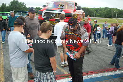 Greg Winchenbach of Jefferson, owner and driver of Crushstation, autographs programs at the Maine Monster Truck Championship in Wiscasset Saturday. (J.W. Oliver photo)