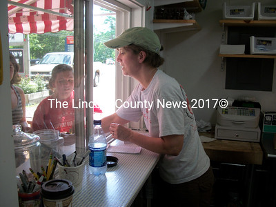 Barb Ganem helps some customers behind the counter at Larson's Lunchbox. Barb, along with her husband Billy and son Eli, served over 200 lobster rolls during a fundraiser for the Ecumenical Food Pantry July 14. (A. Brodsky photo)