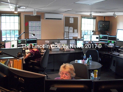 PSAP operators Pamela Reed, of Damariscotta (front), Tara Jones, of Newcastle (left), and Josiah Winchenbach, of Jefferson (right), in the middle of a 12 hour shift at the Lincoln County Communications Center July 23. (A. Brodsky photo)