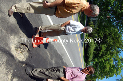 MDOT Commissioner David Cole, left, Sen. David Trahan, center, and MDOT Chief Engineer Dave Bernhardt discuss a sinkhole in the sidewalk on the Bristol Road in Damariscotta. (Alex Toy photo)