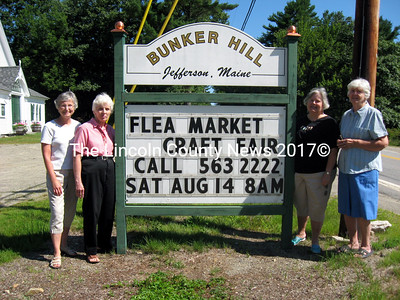 Members of the Bunker Hill Ladies Aid stand with their sign annoucning the flea market and craft fair they will hold in lieu of Jefferson Community Day this year. Members are, from left: Carol Hartman, Joan Ladner, Vice President Lonnie Andersen and President Gladys Johnston. (Samuel J. Baldwin photo)