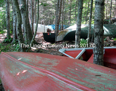 About 30 canoes sit in the woods on the bank of Little Pond in Damariscotta. Landowner Perry Waltz has said the canoes must be removed by Aug. 15. (Samuel J. Baldwin photo)