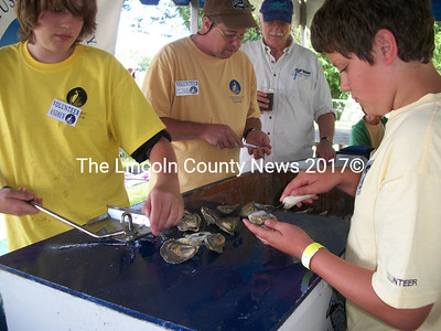 Andrew Arter, of Damariscotta, and Luke Hungtington, of Newcastle, shuck oysters for hungry concert-goers at the Great Salt Bay Music Festival July 31. Arter is using the Aw Shucks Oyster Shucker. Aw Shucks inventor Larry Schneider supervises in the background.  (A. Brodsky photo)