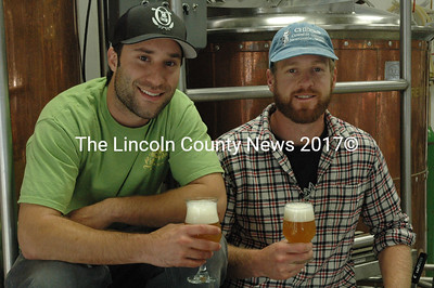 Oxbow owners Geoff Masland, left, and Tim Adams enjoy glasses of their flagship beer, the Farmhouse Pale Ale. (Samuel J. Baldwin photo)