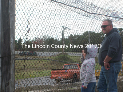 """Autumn Nickerson, 7, and her grandfather Alec """"Buzz"""" Lyons, of West Bath, get close to the track for a mini truck race. With no drivers in the race, Nickerson goes by color: """"My favorite is the pink one,"""" she said. (A. Brodsky photo)"""