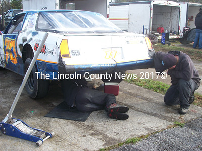 Jared Dunkins (right), of Alfred, works on his wildcat-class car in the crew pit at the Wiscasset Raceway. (A. Brodsky photo)
