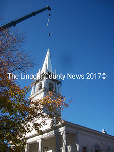 A crane sets the new steeple atop the First Congregational Church in Wiscasset Oct. 17. (A. Brodsky photo)