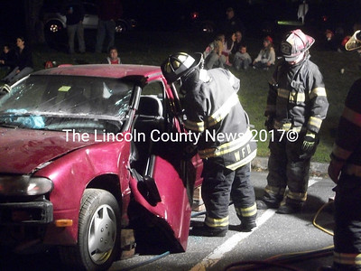 """Members of the Wiscasset Fire Dept. enter a vehicle using the """"jaws of life."""" (A. Brodsky photo)"""