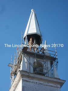 Workers move to set the new steeple in place. (A. Brodsky photo)