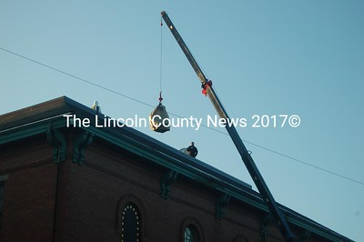 Steel Bolt Construction employees await a bundle of shingles atop Lincoln Hall early Monday morning. (J.W. Oliver photo)