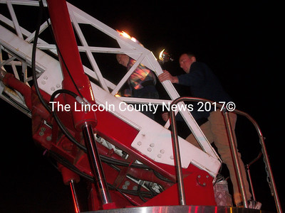 James Pray of the Wiscasset Police lets a student walk up a Wiscasset Fire Dept. aerial ladder. (A. Brodsky photo)