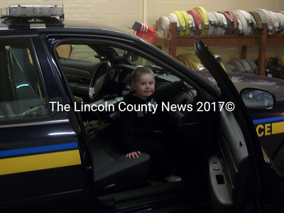 River Fallos, of Auburn, hops into the front seat of a police cruiser at the Wiscasset Fire Dept.'s Open House Oct. 12. (A. Brodsky photo)