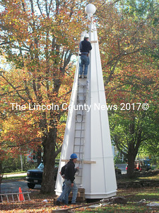Steeplejack George Burgess (above) readies the steeple for its trip to the top of the church tower. (A. Brodsky photo)