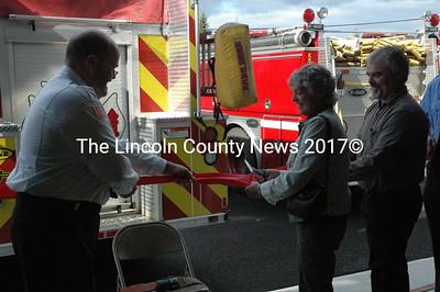 Gwyn Dixon, wife of honoree David Dixon, cuts the ceremonial ribbon with Whitefield Deputy Fire Chief Scott Higgins, left, and Selectman Steve McCormick. (Samuel J. Baldwin photo)