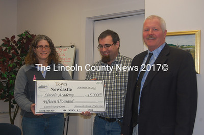 Newcastle selectmen and Lincoln Academy alumni Ellen McFarland and Ben Frey present a $15,000 check to Lincoln Academy Head of School Jay Pinkerton Nov. 14. The selectmen and Newcastle Town Administrator Ron Grenier negotiated the grant as part of a 10-year contract with Time Warner Cable. Time Warner subscribers in Newcastle will pay for the grant in the form of a small, monthly surcharge over the life of the contract. Lincoln Academy plans to use the funds for upgrades to technology at the Parker B. Poe Theater and elsewhere on campus. (J.W. Oliver photo)
