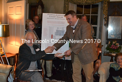 Lincoln County Historical Association President John Reinhardt (seated) accepts a $3000 donation to help repair the Pownalborough Courthouse from Peter Drum and the Lincoln County Bar Association. (Alec Brodsky photo)