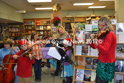 Katy Newell (right) leads her string and flute orchestra at Maine Coast Book Shop during the Wrap It Up Street Festival Dec. 22. (K. Fletcher photo)