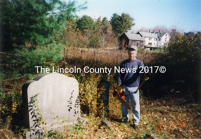 Bob Wilshire cleared the Severance Cemetery in 1999. The Asa Severance family home is shown at the junction of Morgan Hill and Bayview Roads. It was earlier owned by Dr. Moses Baker; later by F. Judson Trask. One of the granite boundary posts is visible next to Wilshire. (Nobleboro Historical Society photo, Oct. 1999)