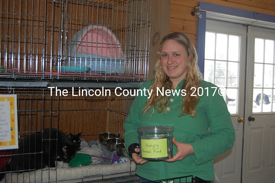 Kate Erkman, manager of the pet center, holds a donation jar for the Hungry Animal Fund. Donors can visit the store or mail contributions. (J.W. Oliver photo)