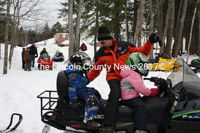 Wiscasset WinterFest volunteer Jeff Robertson (center) secures David Andersson to his snowmobile while his sister Linnea gets ready to help steer. (Matthew Stilphen photo)