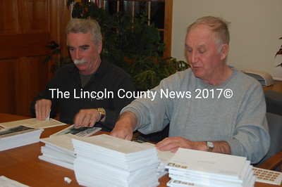 Selectmen Ken Lincoln (left) and Chester Rice affix mailing labels and stamps to South Bristol's 2010 annual reports after the Feb. 24 board meeting. (J.W. Oliver photo)