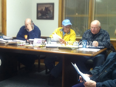Westport Island Selectmen Ross Norton, George Richardson and Jerry Bodmer (left to right) examine bids for the jetty project during a Feb. 28 Board of Selectmen meeting. (Matthew Stilphen photo)