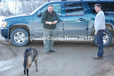Mark Doe, Newcastle ACO, left, and resident George Faux try to lure a loose dog into Doe's truck on Feb. 23. (Samuel J. Baldwin photo)