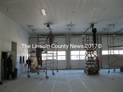 Subcontractors work on door opening mechanisms in the fire station's three-bay apparatus space. At least four vehicles, including Whitefield's tanker and rescue truck, will be located here.