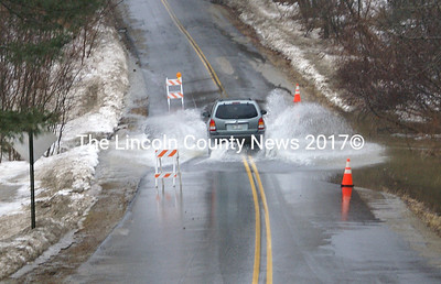 A vehicle runs through a flooded area on McKay Road in Edgecomb. (Steve Edwards photo)