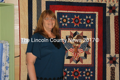 Julie Stegna, manager of Mainely Sewing's new location in Wiscasset, stands in front of a quilt during the store's grand opening May 27. (Matthew Stilphen photo)