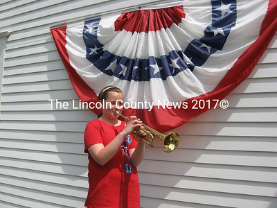 "Hannah Burns, a Whitefield middle school student, plays ""Taps"" on Memorial Day outside the townhouse."