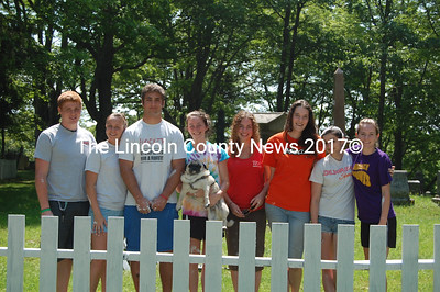 "Lincoln Academy seniors (now alumni) Jan Taliento, Sarah Alley, Sam Stone, Laura Lee (with Lex), Olivia Delisle, Lydia Templeton, Jessica Firth and Celia Howland painted the Glidden Street Cemetery fence (foreground) ""to say thank you to all the taxpayers who pay our tuition."" (J.W. Oliver photo)"