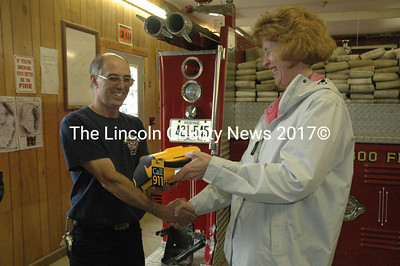 Sara Burns, President of CMP, presents Somerville Fire Chief Mike Dostie with an AED the company donated to the Somerville Fire Department. (Samuel J. Baldwin photo)